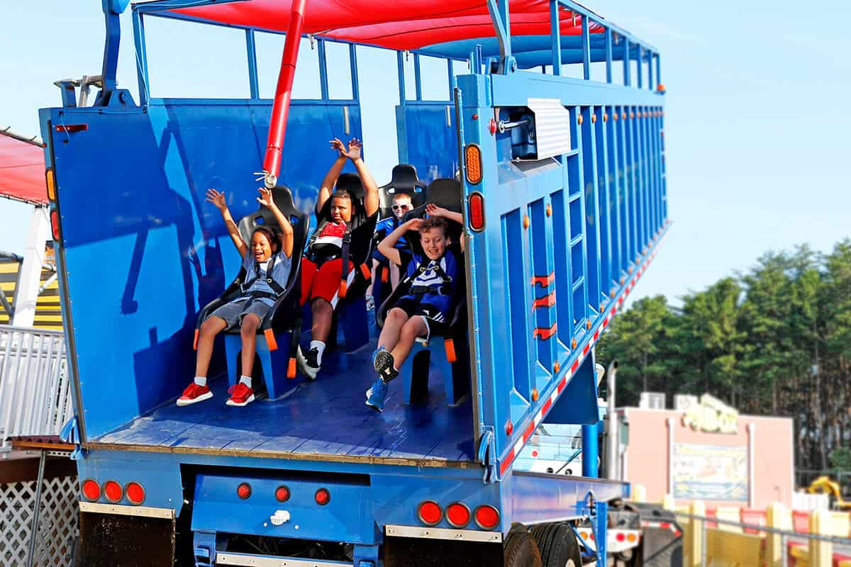 Excited kids are lifted forward in the Greased Beast attraction