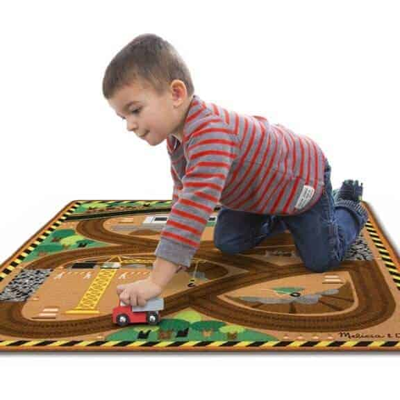 Boy playing on toy work site rug with truck