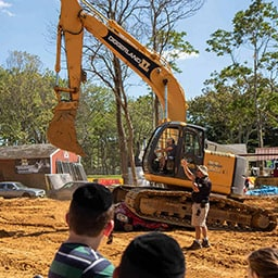 Woman drives excavator and crushes car at XL